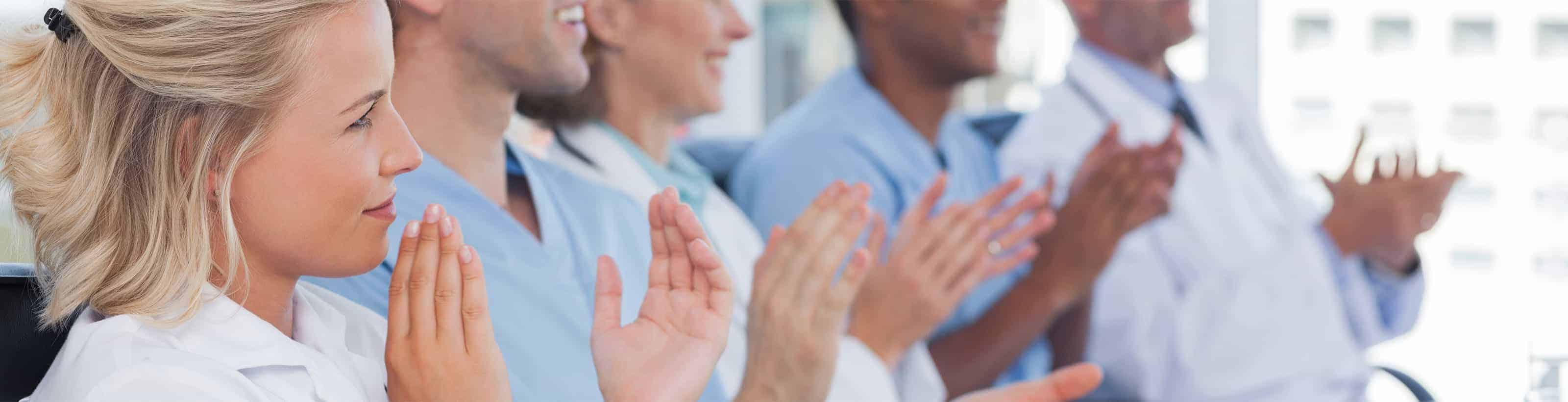 Photo of medical professionals clapping for a presentation