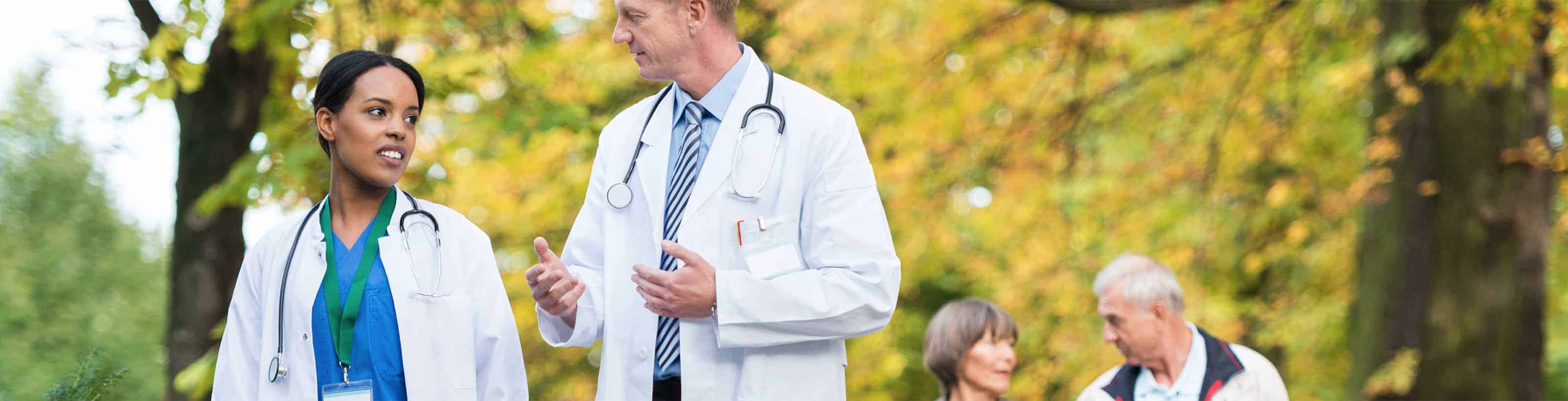 Photo of medical professionals walking through a park
